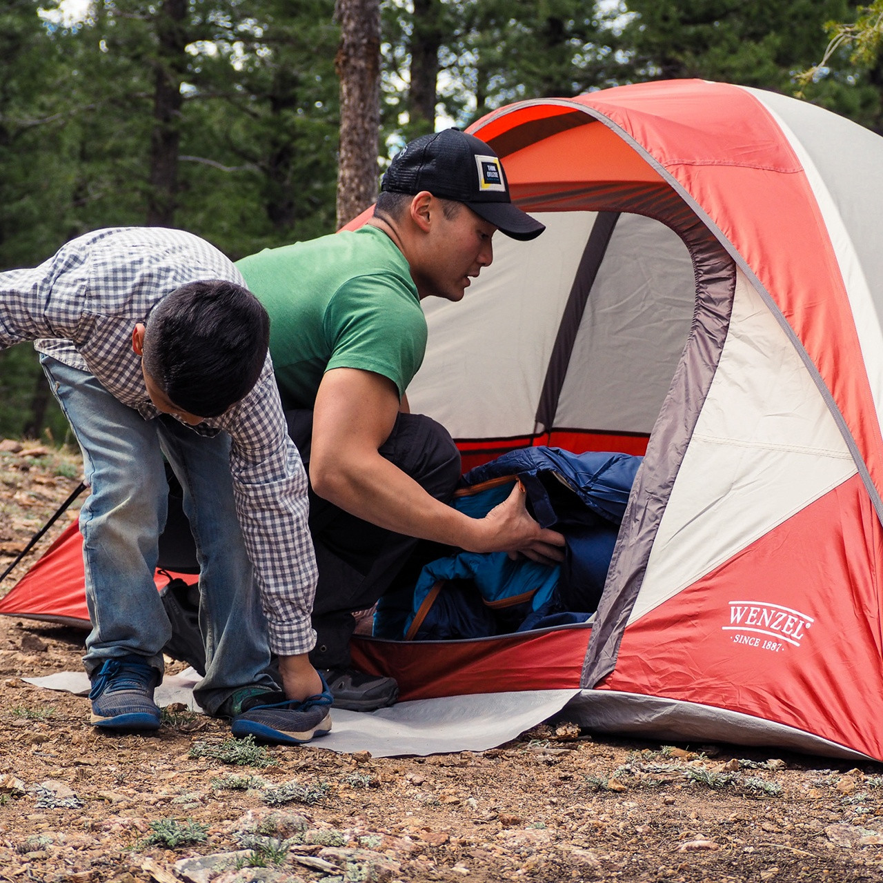 Swole dude putting a sleeping bag into his Wenzel Torry 2 Person Dome Tent
