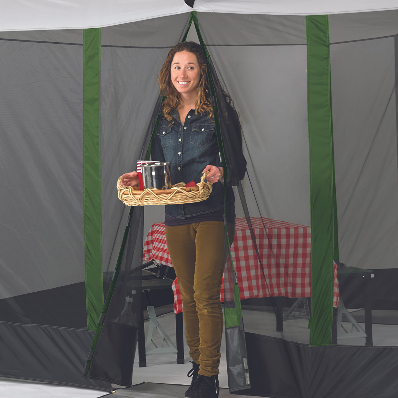 Woman exiting Wenzel Durango Magnetic Screen House, with a tray of tasty food