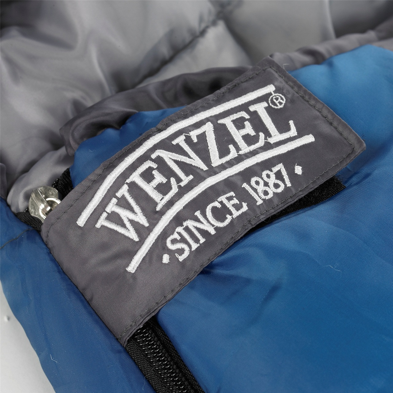 Close up view of the Velcro zipper latch over the zipped showing 'Wenzel since 1887' text