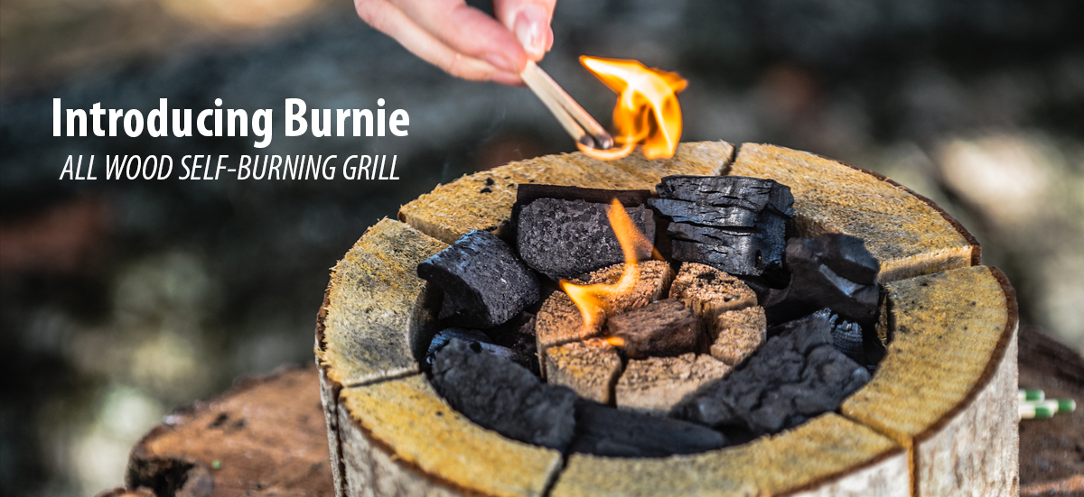 Woman ignites her Burnie disposable wood burning grill for camping.