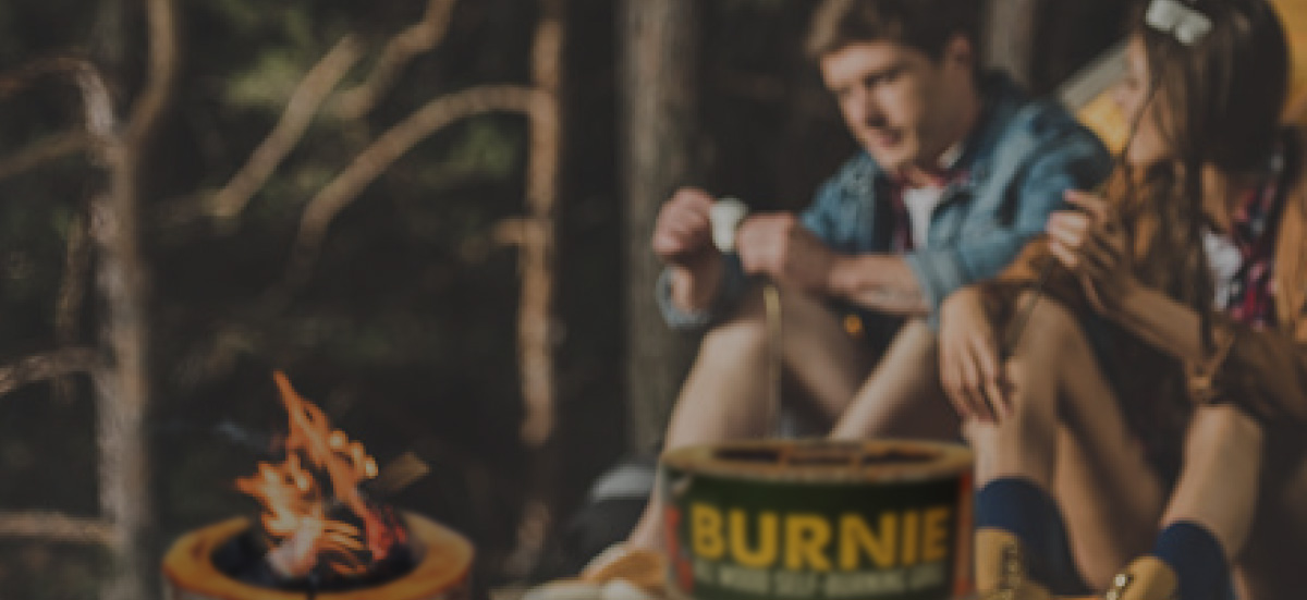 Couple using a Burnie disposable wood burning grill to make s'mores.