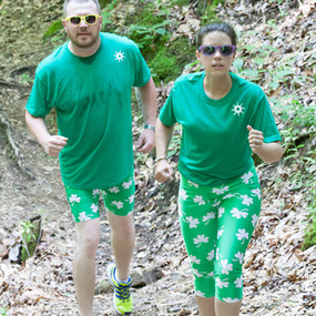 """Special 8"""" shorts in our shamrock print. White four leaf clovers on green background."""