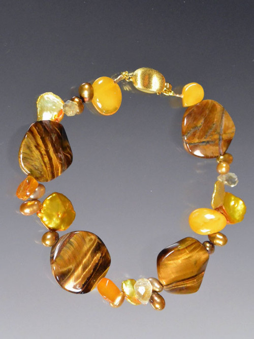 """This bracelet features fluted tiger eye discs, yellow amber, gold pearls  - a perfect transition to fall. 7-1/2"""""""
