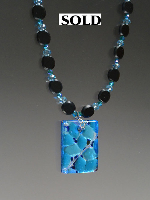 This dramatic necklace features jet glass, Swarovski crystals, and a dichroic aqua blue square pendant. 22""