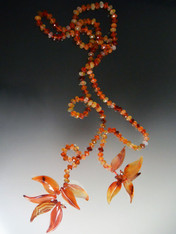 "Another fun colorful layering piece, this lariat features multi-toned faceted carnelian rondels hand knotted with red silk and ending with hand-carved carnelian leaves.  Your imagination can wear this many ways -- just knotted, doubled like a scarf with the ends pulled through or wrapped around your neck.  Note: the carved leaves are delicate so don't bang them against hard surfaces. 48""  ONLY THREE!"