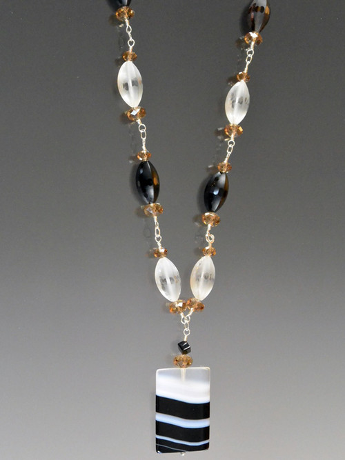 """Every now and then an agate slice naturally occurs with an amazing pattern.  This pendant is such a beauty with natural stripes of black, and white It is the focal point of a sterling wire wrapped necklace with etched white and black crystal.  Totally versatile and stackable. 22"""" pendant 2"""""""