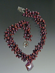 "This luxurious bold collar features multi strands of tiny top drilled wine freshwater pearls  and a ""cosmic"" Swarovski crystal pendant with unique facets that brilliantly reflect light and color like no other pendant in the world (a perfect example of why Austrian crystal can never be duplicated).  A sterling amethyst pearl  clasp completes the picture. 20"" 17-1/2"" twisted. Pendant 1-1/2"" ONE OF A KIND"