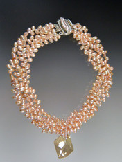 "This luxurious bold collar features multi strands of tiny top drilled pink freshwater pearls  and a ""cosmic"" Swarovski crystal pendant with unique facets that brilliantly reflect light and color like no other pendant in the world (a perfect example of why Austrian crystal can never be duplicated).  A one of a kind mabe pearl sterling clasp completes the picture. 20"" 17-1/2"" twisted. Pendant 1-1/2"""