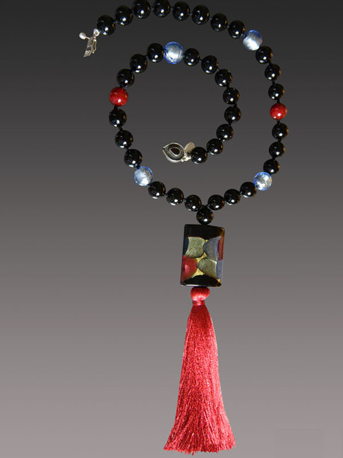 "This statement on trend necklace is all you need to make any outfit stand out. The starting inspiration is an amazing limited edition Venetian arlecchino* rectangle in luscious dots of wine rubino, blue, olive and 24K Gold Foil paired with an ruby silk tassel and hand-knotted Venetian bead necklace. 24"" Silk Tassel 6.5"""