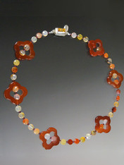 This delightful necklace features rich carnelian quatrefoil stations, Hessionite garnet in colors from pale gold to rich brown with tiny faceted rhodolite garnet and an amber sterling clasp. Perfect to mix with other designs in the collection for an interesting layered look.  18""