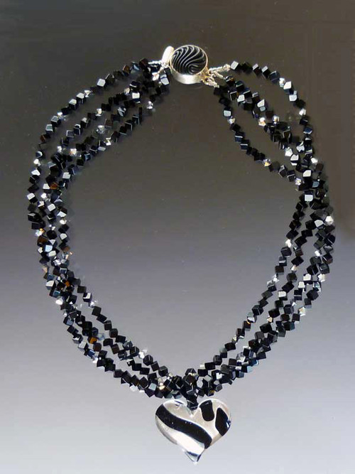 "Two opulent looks in one! Luxuriate in four strands of Grade AAA onyx dice specially ordered for this design randomly spaced with sterling Swarovski crystals.  A dramatic Venetian glass freeform sterling black and silver tiger pattern heart suspended from a circle of onyx beads can be removed for an elegant torsade only look. ONLY TWO  18"" (Longer lengths available on request)"