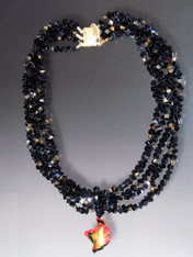 """Luxuriate in six strands of Grade AAA onyx's dice spaced with 24K Swarovski crystals with 24K brushed goldplated clasp. A dramatic Venetian glass swirl centerpiece suspended from a circle of onyx beads can be removed for an elegant torsade look.18"""""""