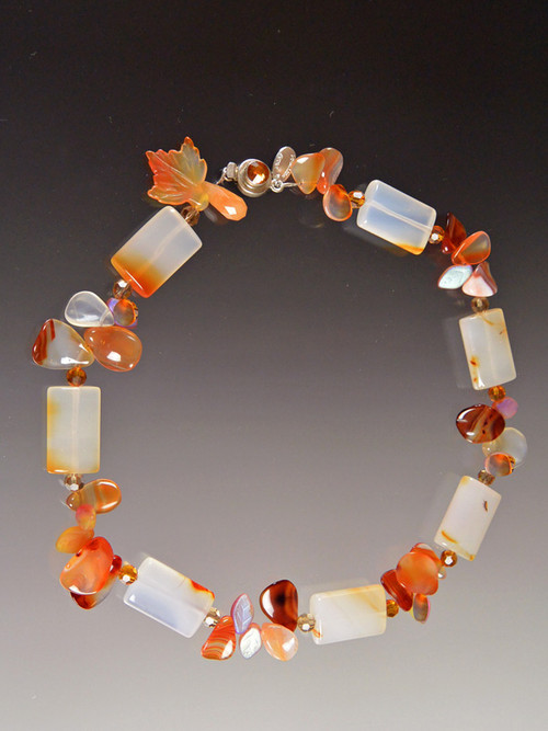 """This delightful collar will lift your spirits and make you glow in the sunny weather.  It features unusually multi-toned carnelian rectangles spaced with precious clusters of glass carved leaves, tourmaline and fire agate, finished off with a complimentary Swarovski Crystal sterling clasp.  18""""."""