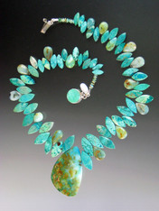 "As they say in French this is a ""piece de resistance!"" Several years ago I found 2 amazing Brazilian peruvian opal pendants -- each a unique artwork with a landscape of pale aqua, deep greens, flashes of copper.  Each is the centerpiece of an equally stunning necklace composed of alternating marquis cut grade AAA chrysocolla and peruvian opal beads. This is very special. Necklace 18"" pendant 2"" x 1.5"""
