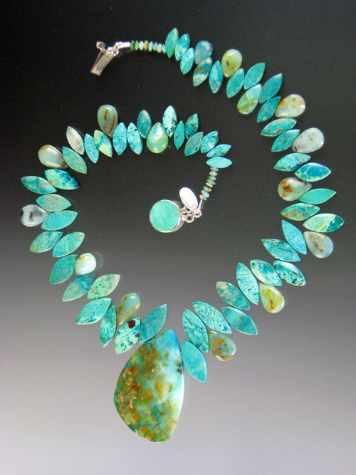 """As they say in French this is a """"piece de resistance!"""" Several years ago I found 2 amazing Brazilian peruvian opal pendants -- each a unique artwork with a landscape of pale aqua, deep greens, flashes of copper. Each is the centerpiece of an equally stunning necklace composed of alternating marquis cut grade AAA chrysocolla and peruvian opal beads.This is very special. Necklace18"""" pendant 2"""" x 1.5"""""""