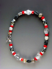 A spectacular collage featuring faceted Brazilian tourmalated quartz, red coral, vintage Bali silver beads, black onyx swirl beads, patterned African horn, and white shell.