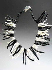 "Alternating natural white and black coral branches dramatically circle your neck in a 18"" collar."