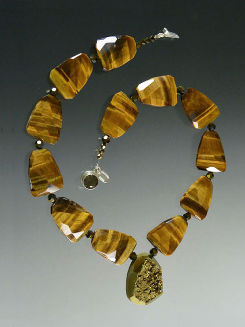 """A bold statement piece featuring faceted tiger eye slices, Swarovski crystals, and a Brazilian titanium coated Gold Pendant. 19"""""""
