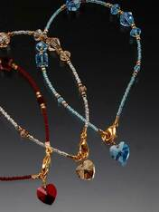 """A dazzling token of love says a lot but costs a little. Rich red Swarovski crytals, 24K vermeil cast toggle clasp,and a dangling Swarovski heart charm! A perfect gift for Valentine or anytime. 7""""-7-1/2"""" Choose red, London topaz blue, or light champagne."""