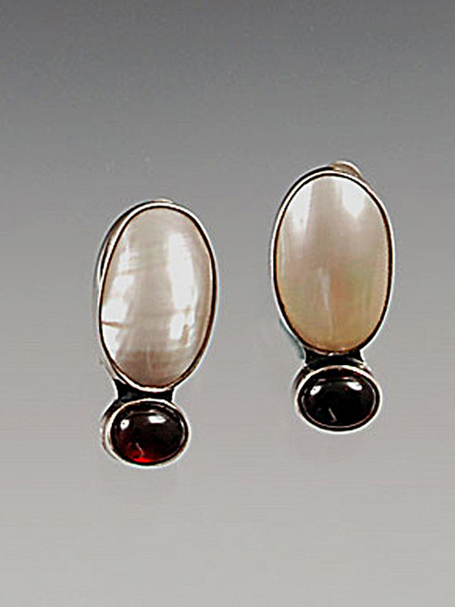 "A luminous mabe pearl rests atop a deep garnet cabachon all hand-set in sterling silver. 1-1/4 x 1/2"" Now clips; convert to posts for an additional $12"