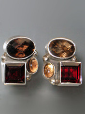 """These striking Amy Kahn Russell one-of-a-kind earrings feature one faceted and one smooth smoky topaz cabochons and a rich faceted garnet stone all bezel set in sterling silver. 1"""" x 1"""" Posts; can be converted to clips for an additional $12."""