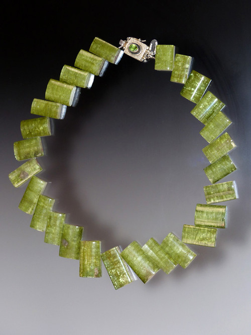 """Many years ago I found many years ago -- an amazing strand of rare Brazilian peridot green tourmaline arranged in a nesting geometric pattern. Green is the classical tourmaline color and within it there are many shades from deep bottle green to fine leek to olive green. This strand is also known as """"rhubarb"""" tourmaline because there are subtle flashes of pink-wine as in watermelon tourmaline. They are the most rare and sought after and have increased in value since I got them.To complement this unusual shade, I finished it with a vintage Peruvian sterling silver peridot clasp. You will never find this anywhere so if you crave truly unique natural pieces, this is for you. 20"""""""