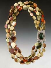 """This magnificent torsade of Imperial Jasper( the finest in the world- found only in Australia) is hand-knotted with pale green silk (20-21""""). A limited edition jade, copper, sterling clasp (1""""x1-1/2"""") can be worn as a center or side highlight. You will be amazed at how many shades this matches. An all time bestseller...cannot be reordered."""
