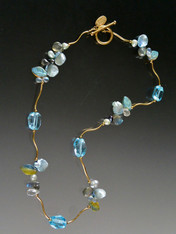 Brazil boasts the world's finest topaz and this blue beauty is no exception. Brilliantly faceted gemstones and precious clusters of freshwater pearls, petal pearls, labradorite, and frosted hand-carved glass leaves nestle between14K curved branches and 14K clasp 17-1/2""