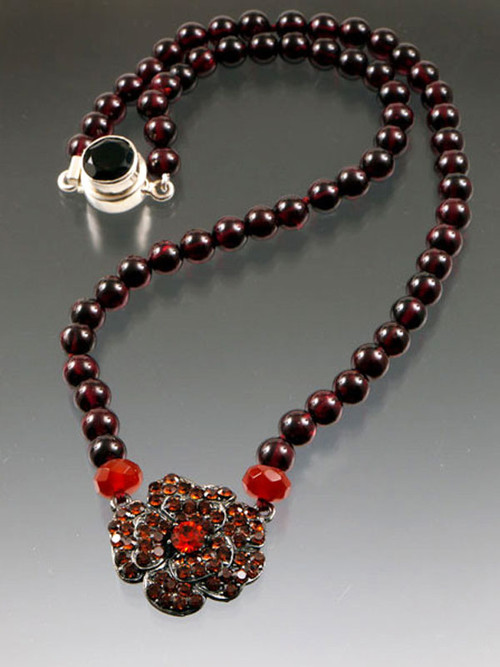 """Many years ago I discovered a vintage French flower necklace with tiny crystals set in black metal. I took it apart and used each precious flower as the centerpiece for a limited edition necklace. This design features grade AAA silk hand-knotted garnet with carnelian rondels and a carnelian toned deco flower. 18"""""""