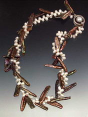 About six years ago I discovered several strands of bronze biwa pearls that were drilled at an unusual angle either intentionally or accidentally.  When entwined with tiny white freshwater pearls the effect is exactly like twigs with sprigs of white blossoms. Held with a vintage mabe pearl sterling clasp. You'll never see this again.  Only three! 17""