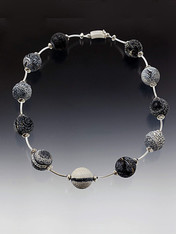 "Circle your neck with a whimsical collar featuring weathered* black and white agate balls, each totally unique in its natural formation, spaced with sterling silver saucer and curved tube beads and a curved sterling clasp.   Perfect for every season and every occasion.  19"" (available longer or shorter)"