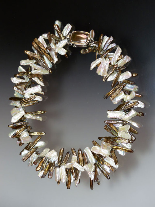 "Want to look as powerful as Elizabeth I?  Want to make a statement with a suit or evening gown? You don't need a fluted  ""ruff"" standing 3"" around your neck. Just don this dimensional collar of intertwined bronze and white  biwa pearls spaced with sparkling tiny Swarovski crystals and a Peruvian mabe pearl sterling clasp for a fabulous effect.   20"""