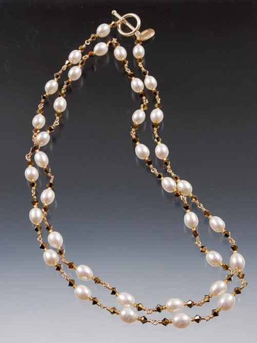 """This delicate 39"""" version of our bestselling dancing pearl necklace features grade AA white freshwater pearls with bronze Swarovski crystals and a 14K toggle clasp. Wear it at least 3 different ways--one long rope, a double strand necklace, or a multi-strand bracelet."""