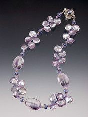 An extraordinary luscious collar of  lilac petal pearls spaced with  large Grade AAA lilac amethyst smooth nuggets, swarovski crystals and 14K.  A custom mabe pearl sterling clasp completes this gorgeous picture.  ONLY TWO!