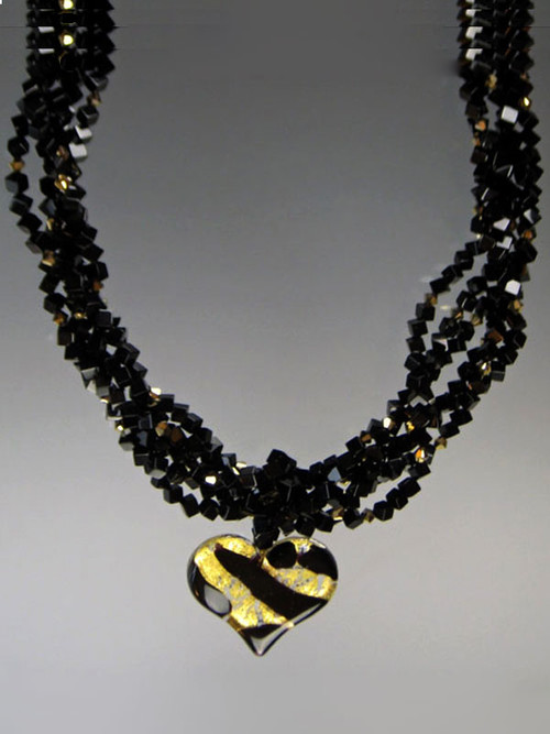 "Two opulent looks in one! Luxuriate in four strands of Grade AAA onyx dice spaced with 24K plated genuine Swarovski crystals.  A dramatic Venetian glass freeform black and gold tiger pattern heart suspended from a circle of onyx beads can be removed for an elegant torsade only look.18"" (Longer lengths available on request)"