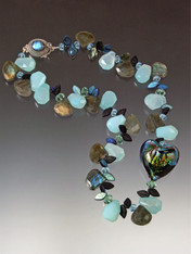 "A marine fantasy of grade AA labradorite, aqua chalcedony, and delicate carved venetian glass leaves frames a 1-1/4"" puffed Venetian glass heart evoking all the colors of the ocean on one side and a marine sunset with streaks of wine on the other. Two reversible looks in this stunning collar! Custom labradorite sterilng clasp! 18"""