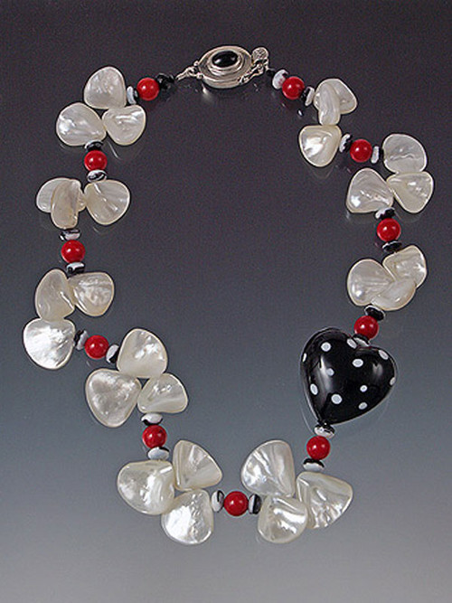 "A whimsical black and white 1-1/4"" puffed polka dot heart adds fun to any occasion. Glowing white mother of pearl fans, red coral beads and custom onyx sterling clasp complete the festive picture! 18"" (ask about longer lengths)"