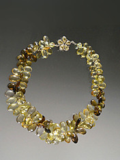"""Many years ago I discovered this amazing strand of Grade AAA faceted gemstone quality multi-toned topaz briolettes shooting off sparks of lemon, olive, brown and other tones. I decided to kept this cluster together in a spectacular collar fit for a queen with a matching topaz silver custom clasp. 19"""""""