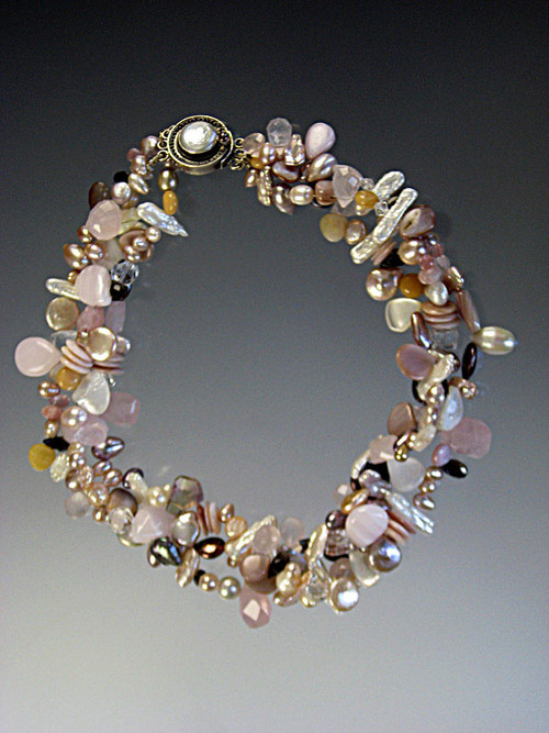 "A delightful torsade of tiny sparkling pink opal, multi-toned and shaped freshwater pearl teardrops, and Swarovski crystals.  No two alike but all fabulous.  Choose one, two or three strands for a spectacular showpiece. One strand 18"" Two and Three Strands 21"""