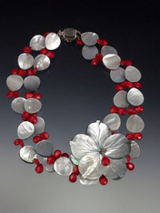 A carved black or white mother of-pearl flower on 2 strands.