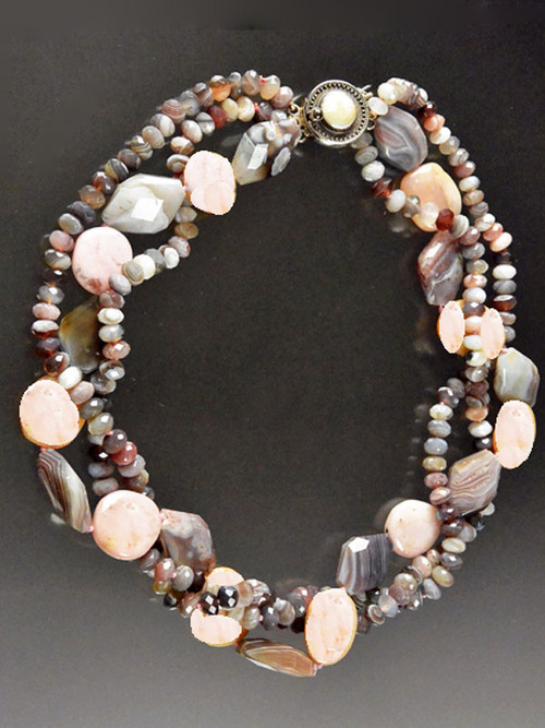 """This lustrous multi-strand torsade features Botswana Agate rondels intertwined with strands of pink opal and botswana agate nuggets. A delightful sublte medley of pink, gray, and silver tones with a rare mabe pearl sterling clasp. 21"""""""