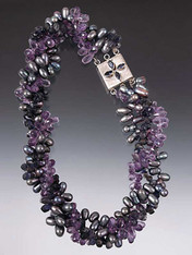 """Opulent and gorgeous!  This dramatic torsade features faceted amethyst and iolite briolettes, peacock freshwater pearls and an iolite sterling custom clasp for a side or center highlight.  20"""""""
