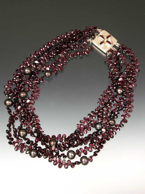 "Take center stage with a magnificent multi-strand sparkler of grade AAA faceted rhodolite garnets starring 12mm freshwater pearls, finished off with a custom sterling garnet clasp.  Available in 5 or 6 strands 20"" Similar design sold in high end Madison Avenue Boutique for $30,000 (with gold clasp)"