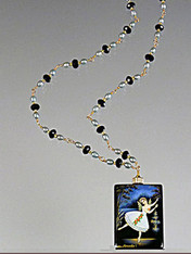 """This hand-painted Russian lacquered miniature features a ballerina/angel floating on a radiant background of deep blues lit by a pool of light. The black onyx pendant (1-3/4"""" x 3/4"""") has been painstakingly covered with many layers of oil paint, egg tempura, gold foil, and lacquer to create the dramatic effect. The pendant, crowned with a 14K gold rondel and 24K Swarovski crystal, hangs from a gold wire wrapped chain of blue freshwater pearls and tiny sparkling Swarovski crystals. 28"""" ONLY ONE."""