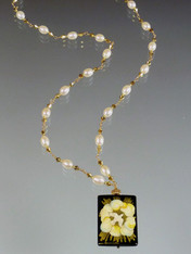 "This hand-painted Russian lacquered miniature features a beautiful white dove circled by gold swirling clouds encased in thin gold strips. The black onyx pendant (1"" x 3/4"") has been painstakingly covered with many layers of oil paint, egg tempura, gold foil, and lacquer to create the dramatic effect.  The pendant, crowned with a 14K gold rondel and 24K Swarovski crystal, hangs from a gold wire wrapped chain of white freshwater pearls and swarovski crytals. 20"""