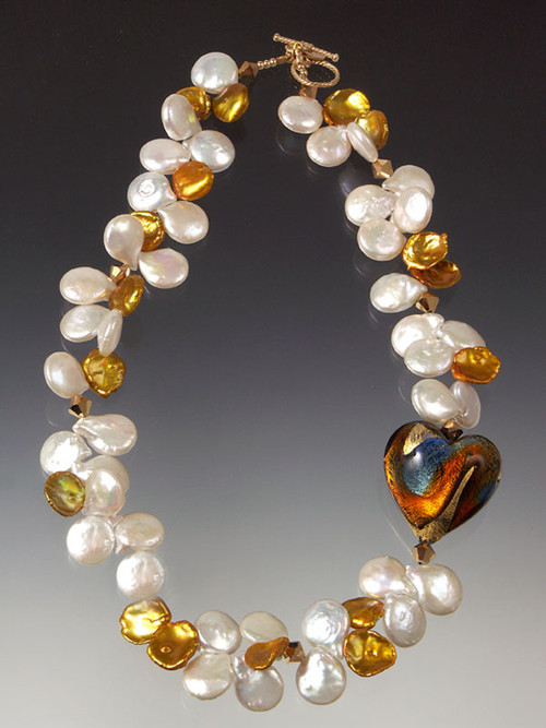 "This luxurious elegant and dramatic necklace features a 1-1/4"" puffed heart of 24K gold blue, orange and garnet evoking a gorgeous sunrise held by opulent white pearls and huge gold petal pearls, Swarovski crystals.18"""