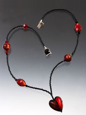 This delicate necklace features a ruby red and deep burgandy heart on a chain of tiny black glass beads with Venetian glass and Swarovski crystal. 17-1/2""