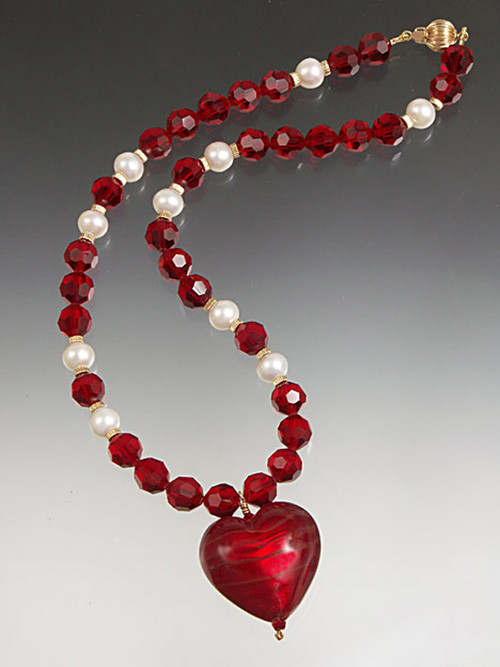 "This dramatic necklace features a 1-1/2"" fire engine red Venetian glass ""puffy"" heart suspended from a chain of matching Swarovski crystals.  18"""