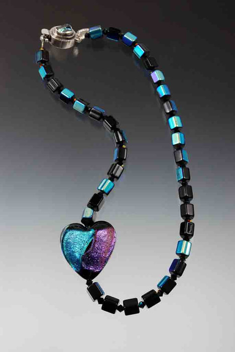 This dramatic statement necklace features a dichroic* venetian glass heart with flashes of purple, aqua, black, gold and green on a chain of vintage iridescent Czech glass faceted cubes spaced with Swarovski crystals.