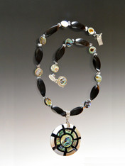 "Make a dramatic statement with this natural black horn swirl, faceted pyrite and abalone pendant necklace. Pendant features mother of pearl, abalone, black horn, and sterling silver in an on-trend geometric pattern.  Necklace 19"" Pendant 2"""
